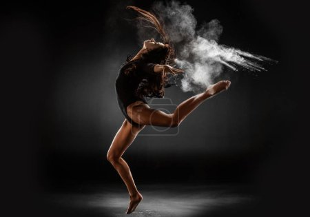Photo for Young ballerina in black bodysuit with talc powder dancing on dark background - Royalty Free Image