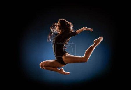 side view of beautiful ballerina in black bodysuit jumping on dark background