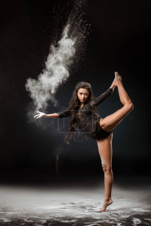 young ballerina in black bodysuit with talc powder dancing on dark background