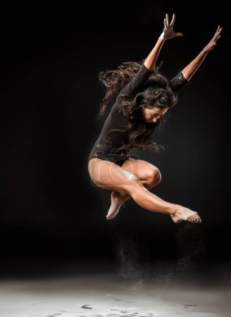 beautiful ballerina in black bodysuit jumping on dark background