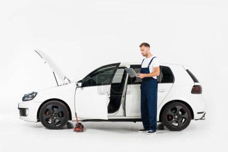 Photo pour Beau garagiste en uniforme bleu à l'aide de portable près de voiture cassée sur blanc - image libre de droit