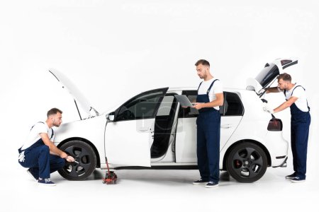 Foto de Mecánico de automóviles, cambio de neumático de coche, usando laptop y busca en el maletero abierto en blanco - Imagen libre de derechos