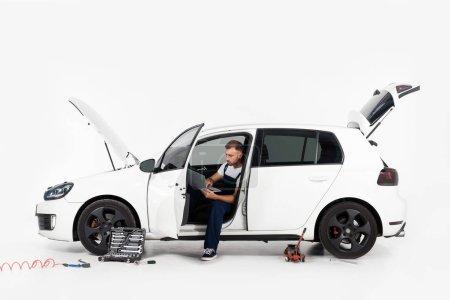 Photo pour Beau mécanicien automobile assis dans une voiture cassée et en utilisant un ordinateur portable sur blanc - image libre de droit