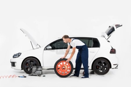 side view of auto mechanic pushing tire to change old one on white