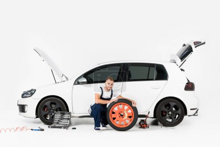 smiling auto mechanic changing car tire and looking at camera on white