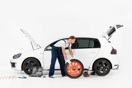 side view of auto mechanic in blue uniform changing car tire on white