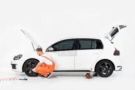 auto mechanic in orange uniform changing car tire on white