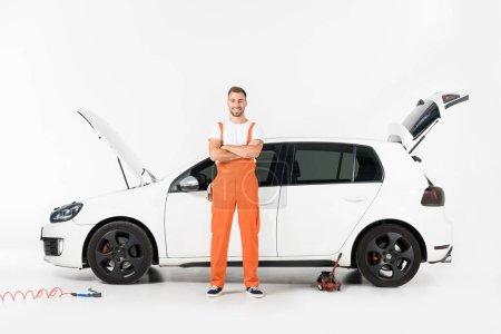 Foto de Sonriendo de pie mecánico auto guapo con cruzado armas cerca de coche rota en blanco - Imagen libre de derechos