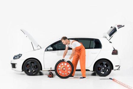 auto mechanic pushing car tire on white