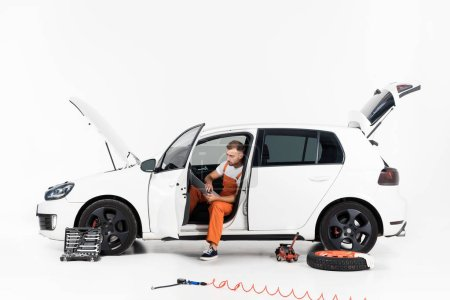 Foto de Mecánico de automóviles guapo usando laptop en coche rota en blanco - Imagen libre de derechos