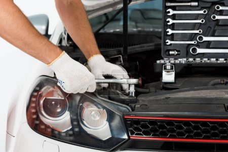 cropped image of auto mechanic auto mechanic repairing car with wrench on white