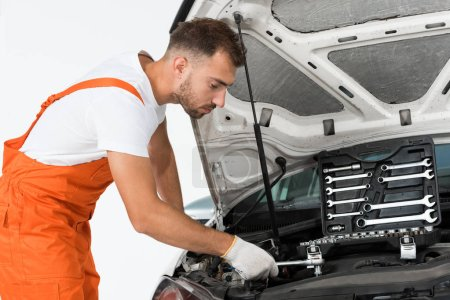 side view of handsome auto mechanic auto mechanic fixing car with wrench on white