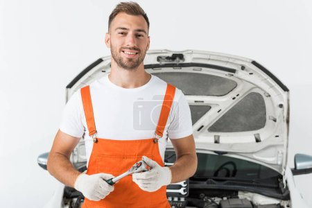 Photo pour Sourire beau mécanicien automobile tenant clé à molette près de la voiture sur blanc - image libre de droit
