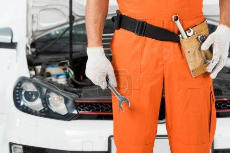 Photo pour Image recadrée de mécanicien automatique tenant clé près de la voiture sur blanc - image libre de droit