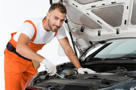 handsome auto mechanic auto mechanic repairing car with wrench on white
