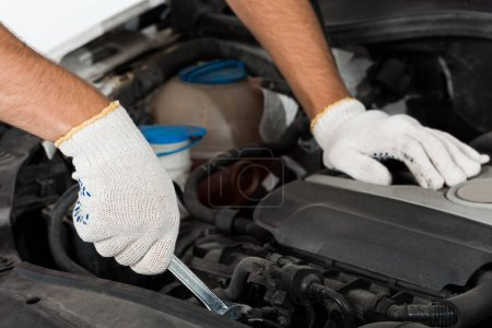 cropped image of auto mechanic repairing car with wrench