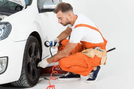 Photo for Handsome auto mechanic inflating tire and checking air with gauge pressure on white - Royalty Free Image