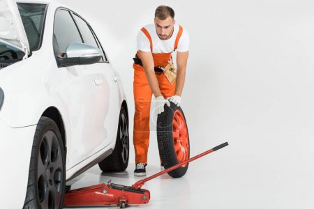 auto mechanic rolling tire to car on white