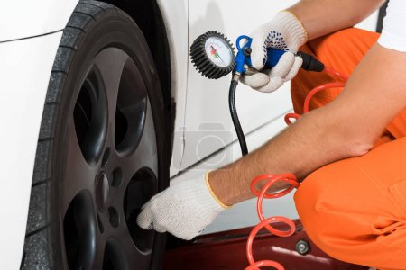 Photo for Cropped image of auto mechanic inflating tire and checking air with gauge pressure - Royalty Free Image