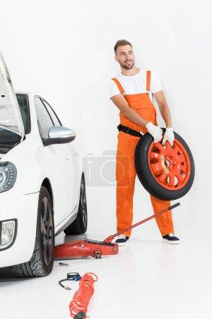 auto mechanic in orange uniform carrying car tire on white