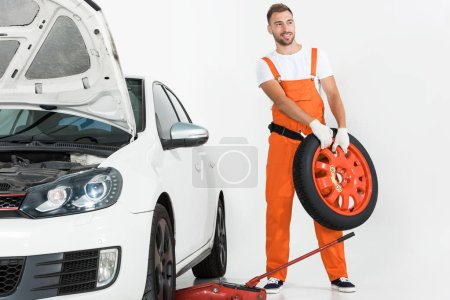 Photo for Auto mechanic carrying car tire on white - Royalty Free Image