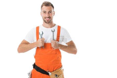 Photo pour Souriant beau garagiste en uniforme montrant les clés isolés sur blanc orange - image libre de droit