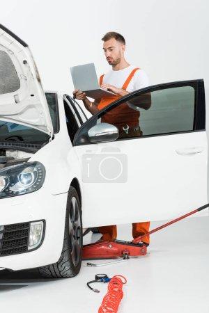 handsome auto mechanic in orange uniform holding laptop near broken car isolated on white