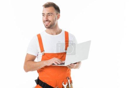 Photo for Portrait of handsome auto mechanic in orange uniform holding laptop isolated on white - Royalty Free Image