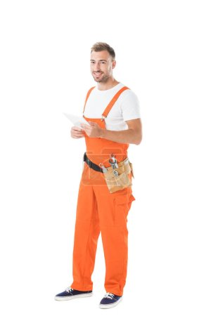 smiling handsome auto mechanic in orange uniform holding tablet isolated on white