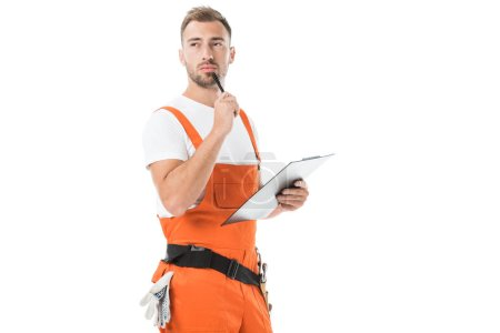 Photo for Pensive handsome auto mechanic in orange uniform holding clipboard and looking away isolated on white - Royalty Free Image
