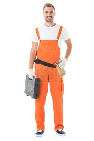 smiling handsome auto mechanic in orange uniform holding toolbox isolated on white