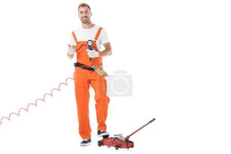 handsome auto mechanic in orange uniform holding gauge pressure isolated on white
