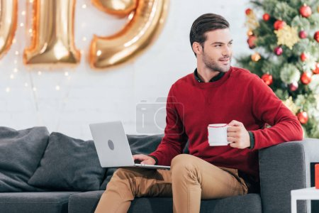 smiling man with cup of coffee using laptop on christmas eve