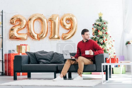handsome man with coffee using laptop on sofa at home with christmas tree and 2019 golden balloons