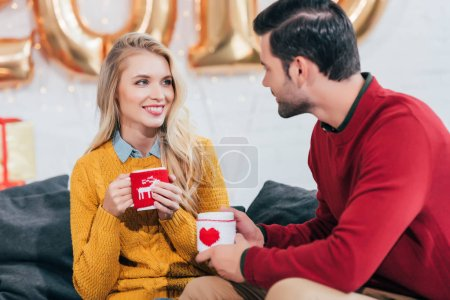 happy couple holding christmas coffee cups and looking at each other