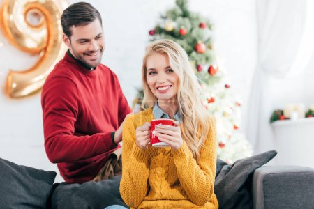 beautiful happy woman holding coffee cup while man looking at her at home with christmas tree