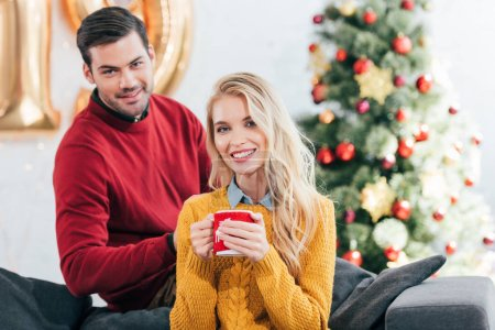 smiling woman holding coffee cup while man sitting near at home with christmas tree