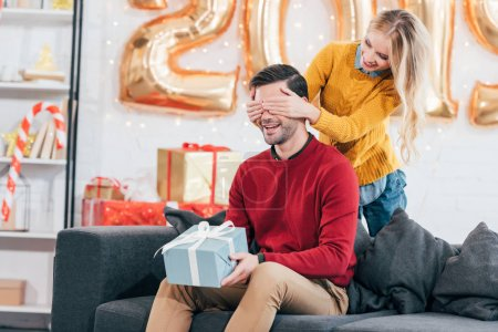 girl closing eyes and making surprise with new year present for boyfriend at home with 2019 golden balloons