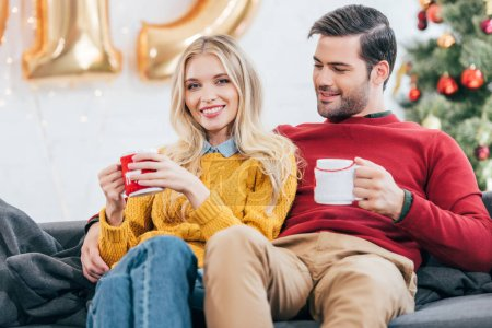 couple holding christmas coffee cups and resting at home together