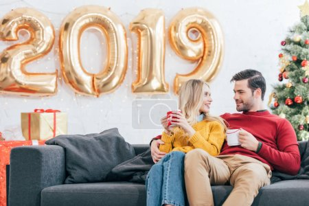 couple holding coffee cups and looking at each other at home with 2019 new year golden balloons