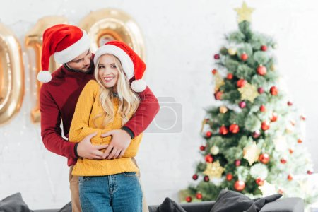 happy man embracing his smiling girlfriend at home with christmas tree