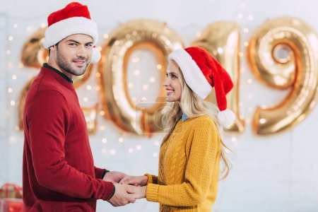smiling couple in santa hats holding hands at home with 2019 new year golden balloons
