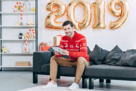 smiling man using digital tablet while sitting on sofa with 2019 golden balloons for new year
