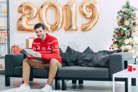 happy man using digital tablet during 2019 new year