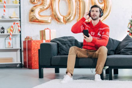young man listening music with headphones and smartphone on 2019 new year