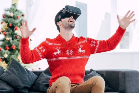 excited man gesturing and using virtual reality headset during christmas eve