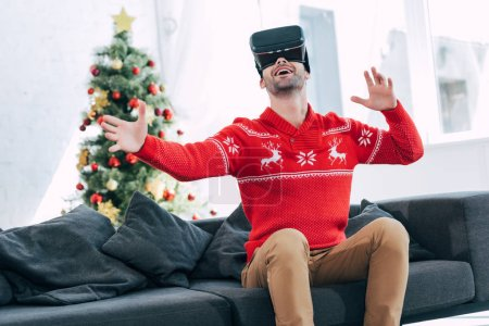 happy man gesturing and using vr headset, christmas tree on background