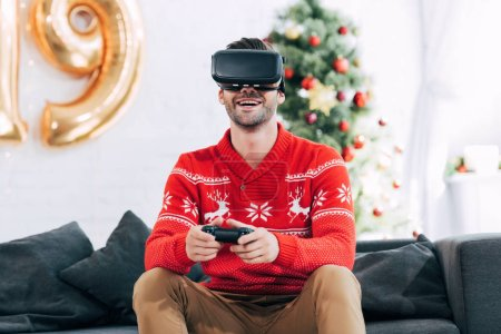 happy man with virtual reality headset and joy pad playing video game during 2019 new year