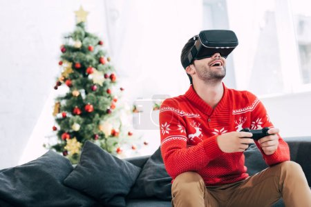 excited man playing game with virtual reality headset and joy pad on christmas eve