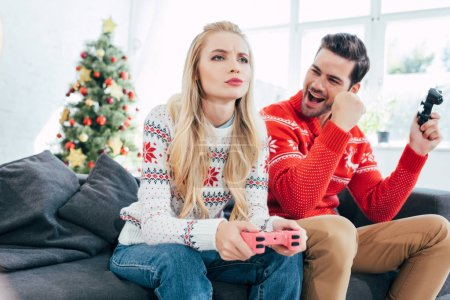 young couple playing video game with joysticks at home with christmas tree